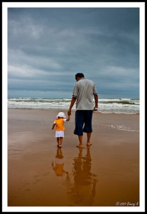 Father walking on the beach with his child