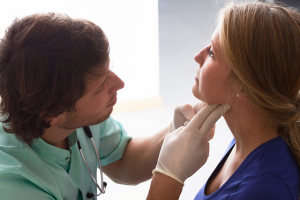 Photo of a nurse looking at a womans neck