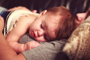 Image of a sick baby girl lying on her mother
