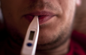 A man takes his temperature when feeling ill.