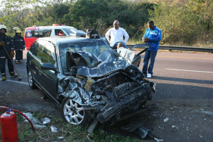 Men standing by the scene of a motor vehicle accident