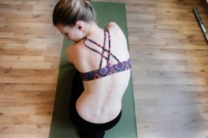 Woman-Sitting-On-Yoga-Mat-In-Workout-Clothes
