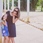Woman and daughter blowing kisses outdoors