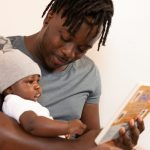 Man reading a book to to a baby sitting in his lap.