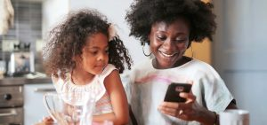 Woman and daughter looking at a smartphone together.